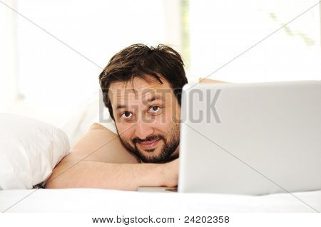 Man in sleeping bed using  laptop
