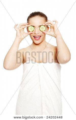 Portrait of the beautiful girl covering her eyes with a slices of a cucumber, isolated on white