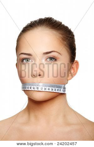 Portrait of a young woman with a white measuring tape covering the mouth