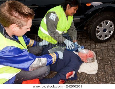 Sanitäter helfen, ein Auto-Absturz-Opfer mit einer Sauerstoffmaske (Ärmel, die Abzeichen durch einen anderen ersetzt wurden