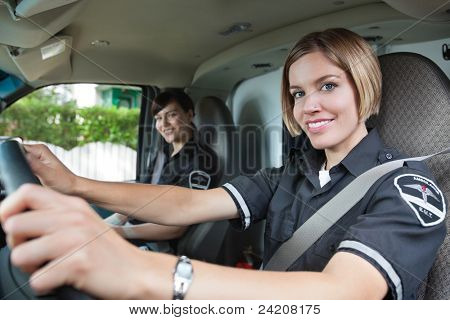 Portrait of happy female paramedic driving ambulance with team member in background