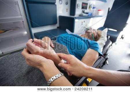 Detail of EMT worker measuring pulse on senior woman patient in ambulance