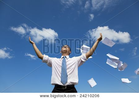 relaxed businessman throwing away papers to the sky