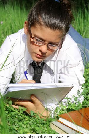 Young Student Girl With Glasses Studying Outdoors