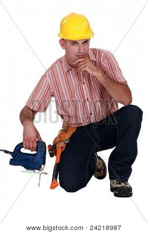 Confident worker kneeling with band saw