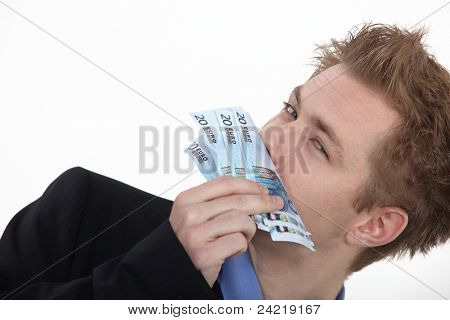 Successful business man smelling money