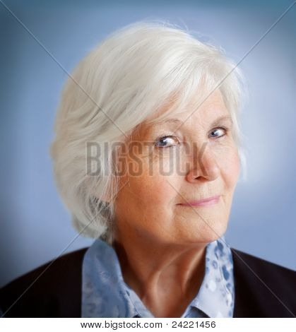 Senior lady portrait on blue background, looking humorous