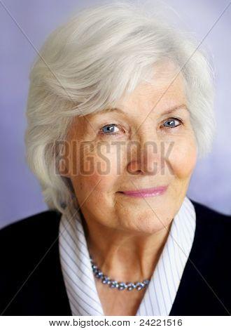 Senior woman portrait on purple background with necklace