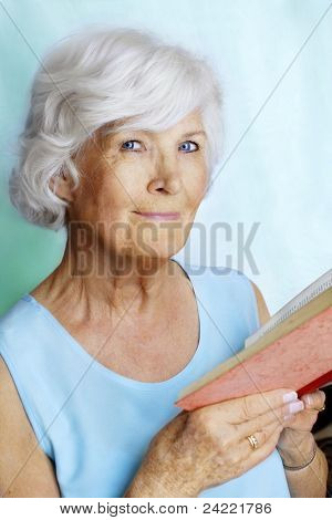 Senior lady holding a book for reading, cyan colors