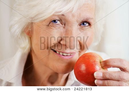 Happily senior woman holding red apple