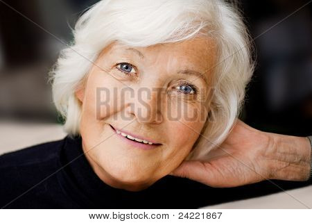 Senior woman portrait, smiling with hand on neck