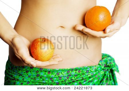 Woman holding an apple and one orange in front of her body,isolated on white background