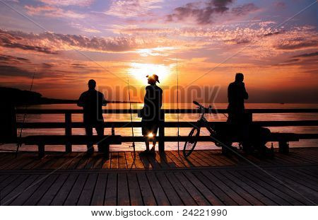 Three Angler standing on a bridge in the sunrise, back lite,