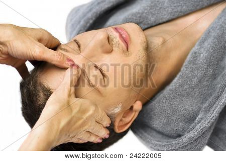 Ältere Mann auf dem Rücken liegend wird Massage, Reiki, Akupressur im Gesicht, Fokus auf Gesicht und Hände