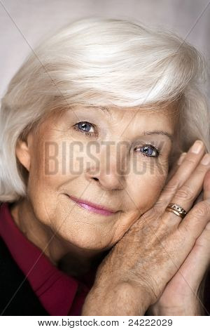 Senior woman holding hands on cheek