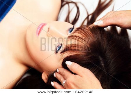 Young woman lying on her back, gets massage,reiki,acupressure on her head,macro-shot, focus on left eye