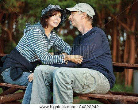 Middle-age couple enjoying togetherness, sitting on a bench in the forest, looking at each other tenderly