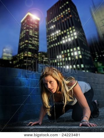 Fashion portrait of sexy female model with skyline urban background at night