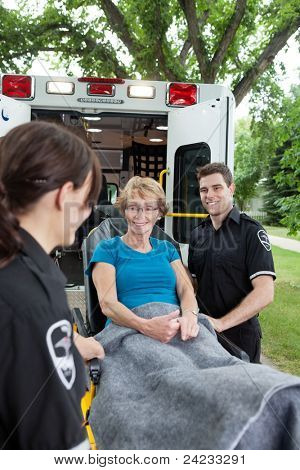 Two ambulance workers pushing a happy senior woman on a stretcher