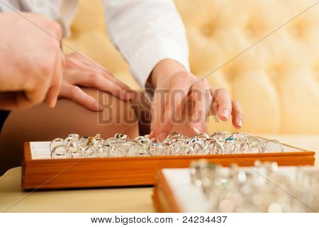 Couple choosing wedding rings at a jeweller