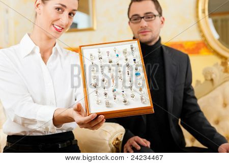 Man choosing a ring at the jeweller and gets consultancy by a shop assistant