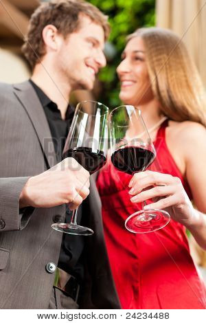 Couple, man and woman, at wine tasting in a restaurant, each with glass of red wine in hand
