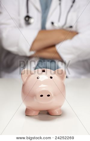 Female Doctor with Folded Arms Behind Piggy Bank Abstract.