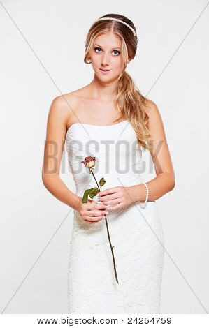 beautiful young bride with flower posing over grey background