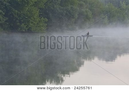 fisherman in a boat on a river in the morning, Ukraine