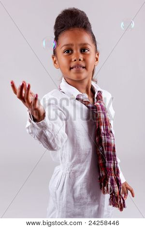 Little African Asian Girl playing with Soap Bubbles