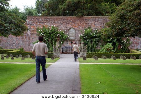 Man & Teenager Walking In A Path In A Cemetery/ Graveyard For Pets