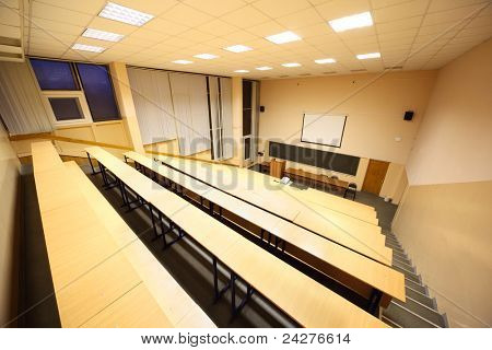 Large classroom, university lecture hall; big blackboard, wooden desks and benches