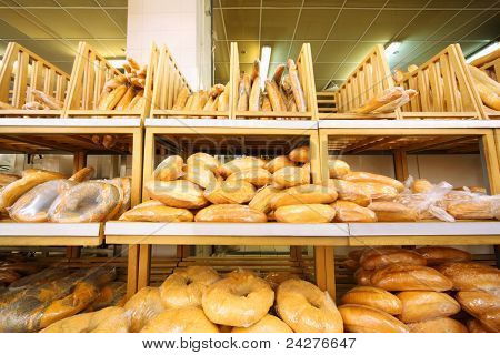 lots of fresh crisp loaves of bread on shelves in store; abundance of delicious soft bread