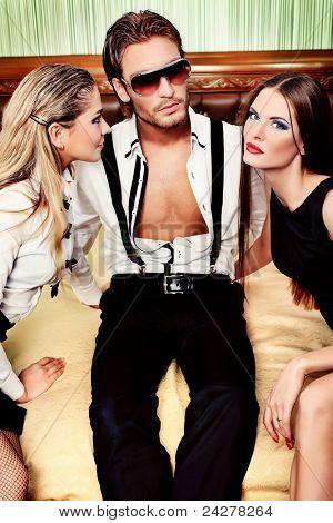 Retrato de un hombre guapo de moda con dos encantadoras mujeres posando en el interior.