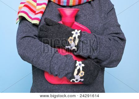 Photo of a woman holding a red hot water bottle to her chest whilst wearing hand kniitted woolen gloves trying to keep warm, good image for winter illness or warmth related themes.