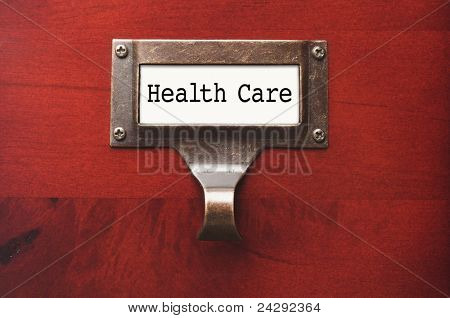 Lustrous Wooden Cabinet with Health Care File Label in Dramatic LIght.