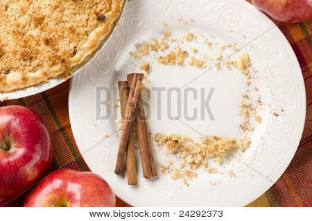 Overhead Abstract of Apples, Cinnamon Sticks, Pie and Empty Plate with Remaining Crumbs Cleared Into Rectangular Copy Room Space and Fork - Ready for Your Own Message.
