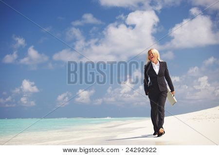business woman with briefcase walking on the desolate ocean coast