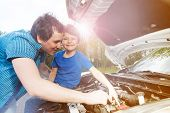 Portrait Of Young Father Repairing Engine While His Little Son Sitting On Opened Hood Of Broken Car poster