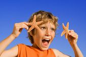 Child Having Fun With Starfish On Summer Vacation