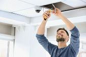 Technician Installing Cctv Camera On Ceiling Indoors poster