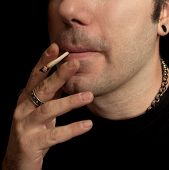 stock photo of marijuana cigarette  - A close cropped image of a man smoking a marijuana joint - JPG