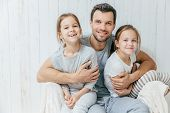 Father And Kids. Paternity Concept. Handsome Unshaven Affectionate Dad Embraces His Two Pretty Dauht poster