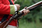 stock photo of revolutionary war  - British Revolutionary War reenactor loading his musket - JPG