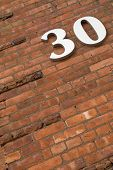 picture of commercial building  - Detail of an urban Brick building with the number 30 on it - JPG