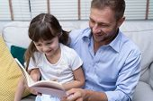 Cute Little Girl And Her Handsome Father Reading A Book And Smiling Together At Home.happy Fathers  poster