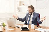 Surprised Businessman Looking At Laptop At His Office Working Place. Portrait Of Middle-aged Employe poster