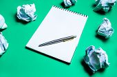 White Notebook With Pen On A Green Background Among Paper Balls. The Concept Of Generating Ideas, In poster
