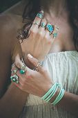 closeup of young woman hands with  lot of boho style jewrly, rings and bracelets outdoor summer day poster