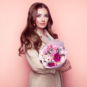 Brunette Young Woman In Stylish Greatcoat. Girl In Beige Coat With Bouquet Of Flowers. Model With Lo poster